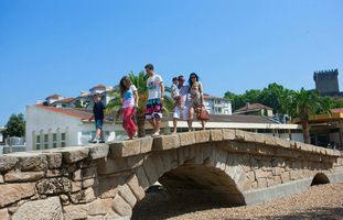 Family on Roman bridge in Chaves, Portugal